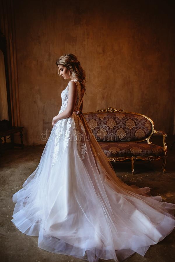 Beautiful blonde bride woman in a gorgeous wedding dress, fashion beauty portrait. In interior stock image