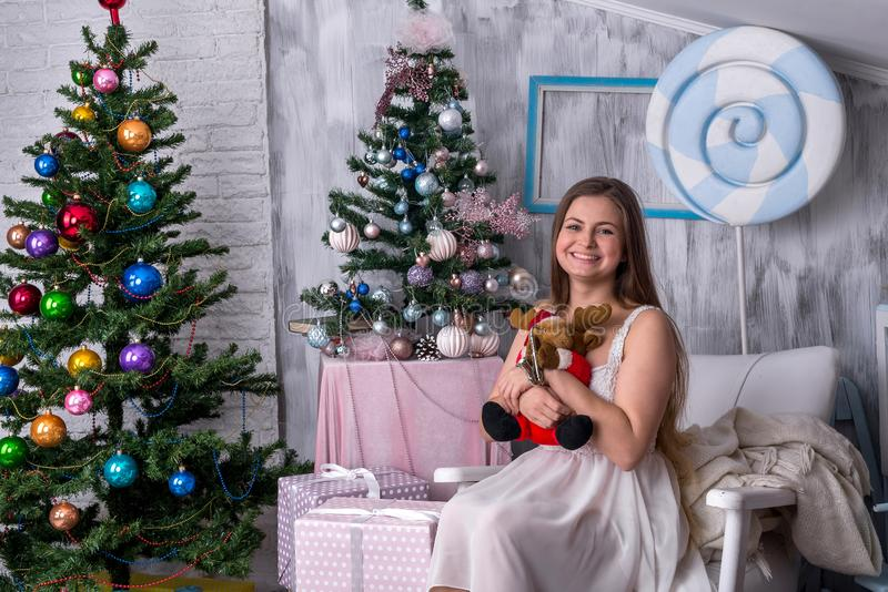 Beautiful blonde in christmas studio with toy `elk stock images