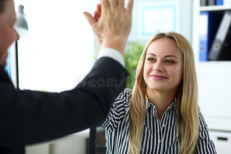 Beautiful blonde clerk giving high five to male customer stock photo