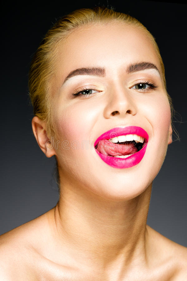 Beautiful blonde with colorful pink lips sticking out her tongue royalty free stock image