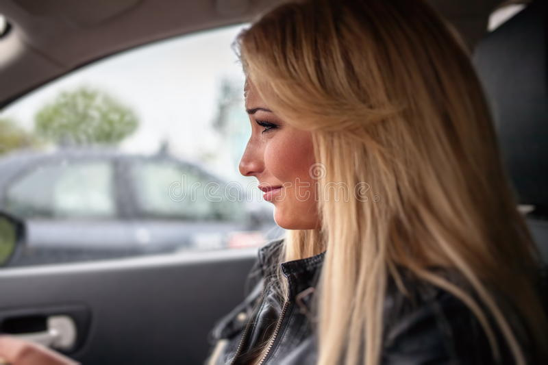 Beautiful blonde is crying behind the wheel of a car. stock photo