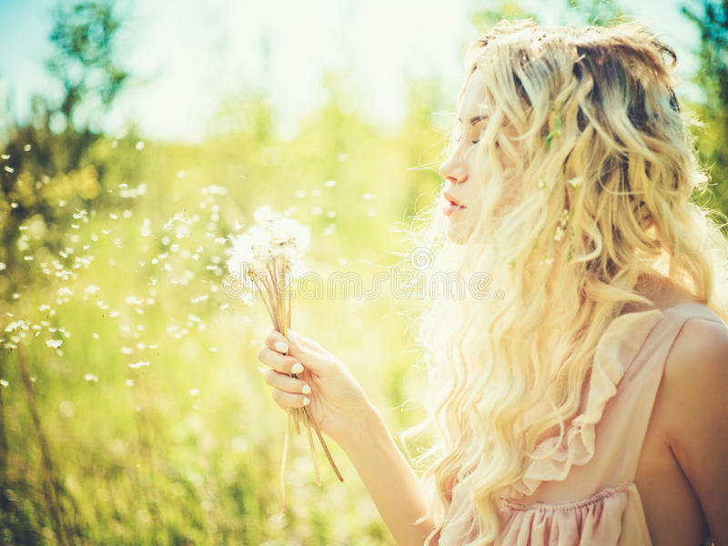 Beautiful blonde with dandelions stock image