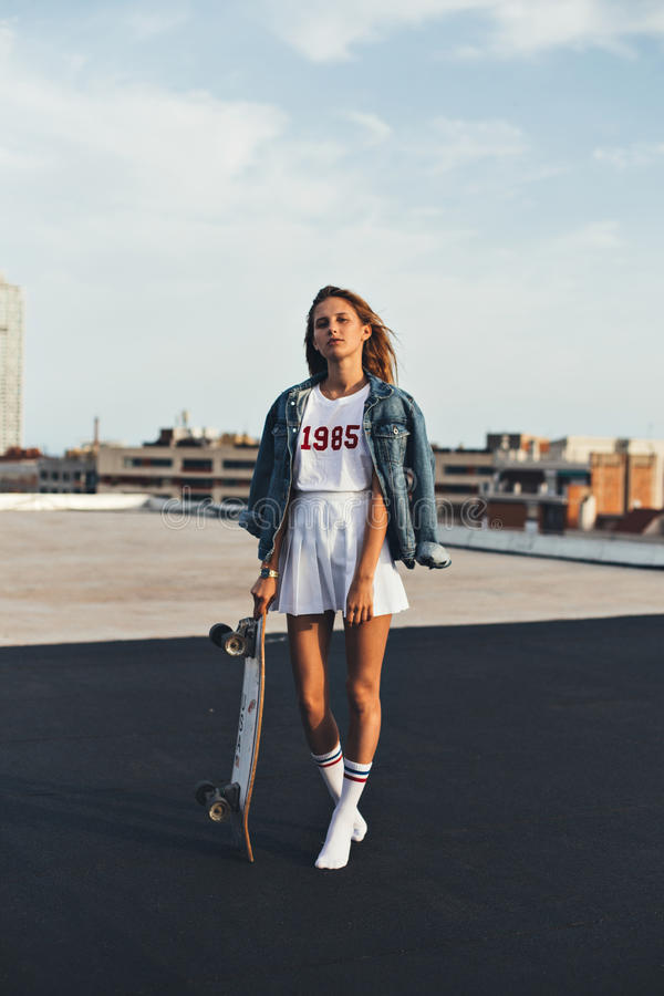 Beautiful blonde in denim jacket with skateboard. Tall hipster blonde model in a casual hipster millenial outfit stands on the top of urban city rooftop with a royalty free stock photography