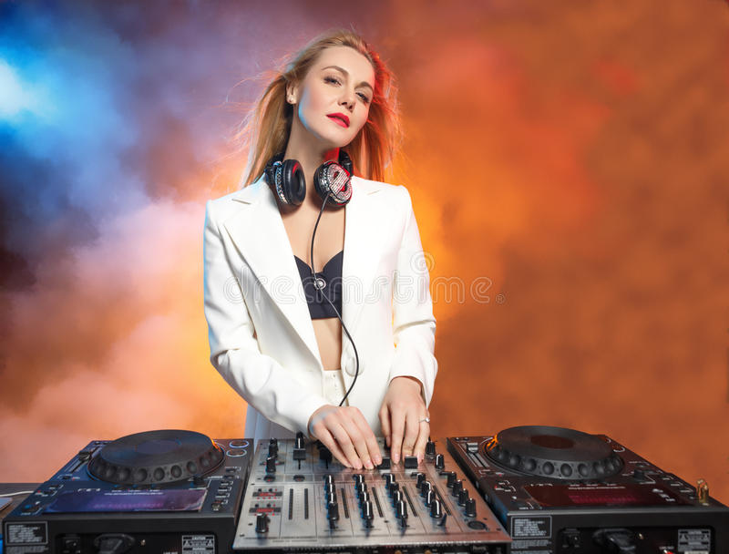 Beautiful blonde DJ girl on decks - the party. Beautiful blonde DJ girl on decks on the party on the background of orange smoke royalty free stock photo