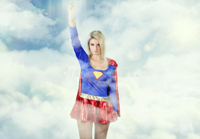 Beautiful blonde dressed as a super hero. Flying in the sky royalty free stock photo