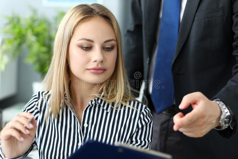 Beautiful blonde female clerk talking with male colleague royalty free stock photos
