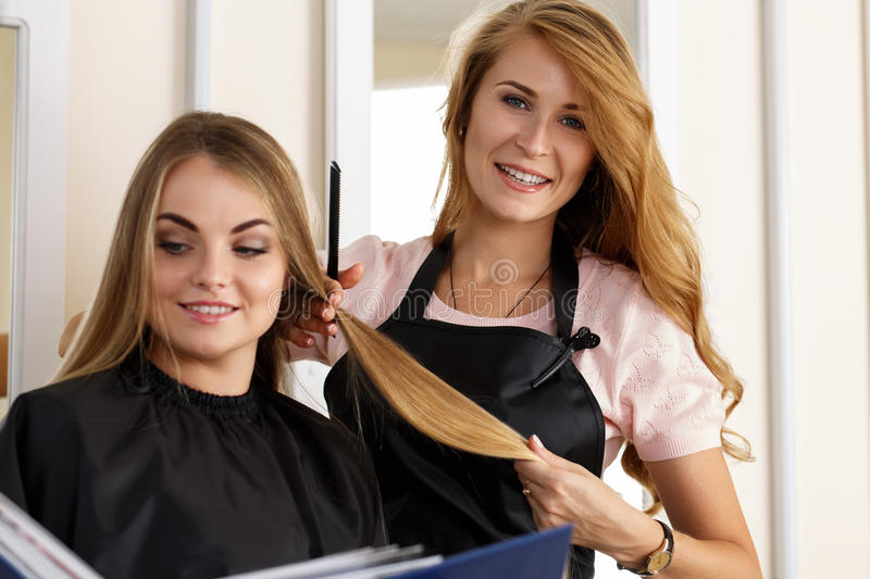 Beautiful blonde female hairdresser holding lock of hair in hand. S and picking proper hairdo to smiling long haired customer. Hairdresser salon, barber shop royalty free stock photos