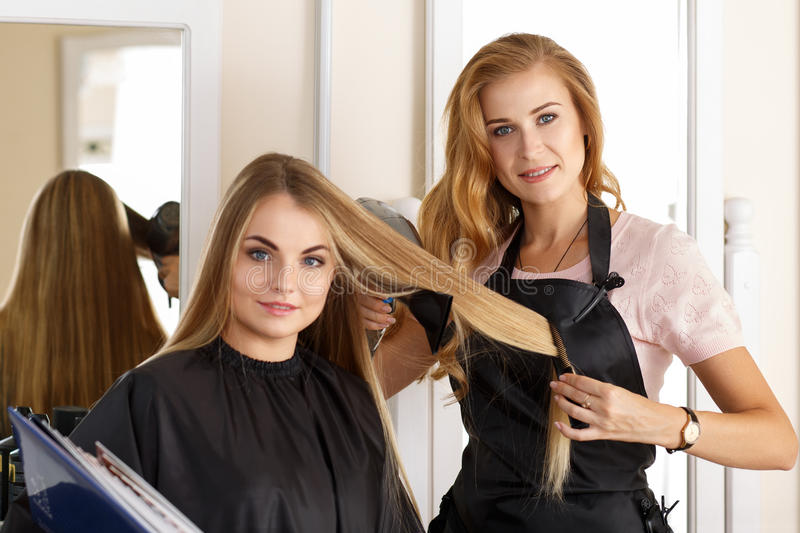 Beautiful blonde female hairdresser holding scissors, comb and h stock photos