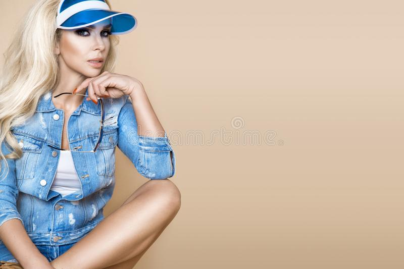 Beautiful blonde female model wearing a denim jacket and shorts stock images