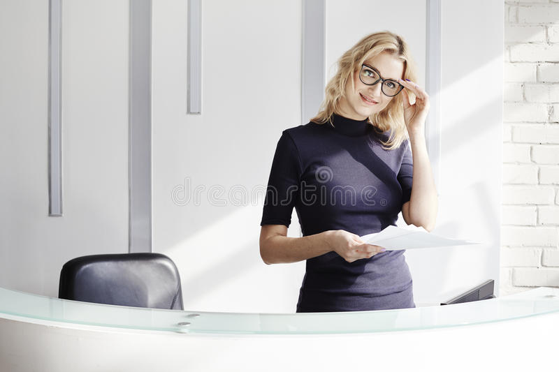 Beautiful blonde friendly woman behind the reception desk, administrator talking by phone. Sunshine in modern office. stock photos