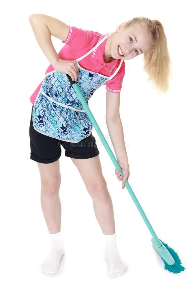 Beautiful blonde girl in apron sweeping floor royalty free stock photo