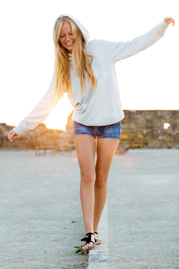 Beautiful blonde girl balancing on a curb in the city. stock image