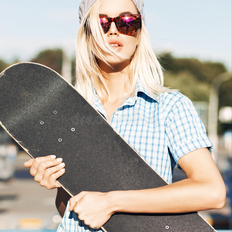 Beautiful blonde girl in beanie hat and leopard sunglasses with royalty free stock photo