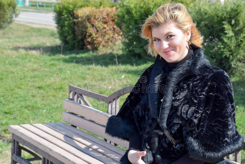 A beautiful blonde girl in a black fur coat sits on a bench stock image