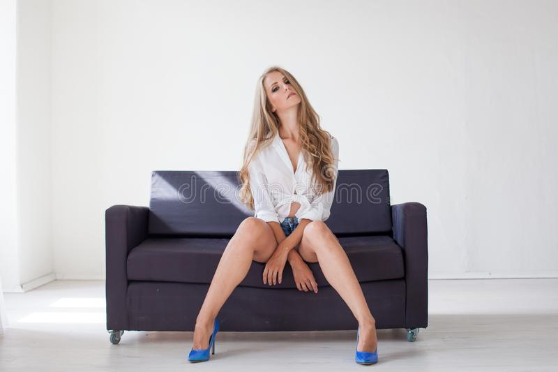 Beautiful blonde girl with blue eyes sitting on the couch in a white room 1 stock photography
