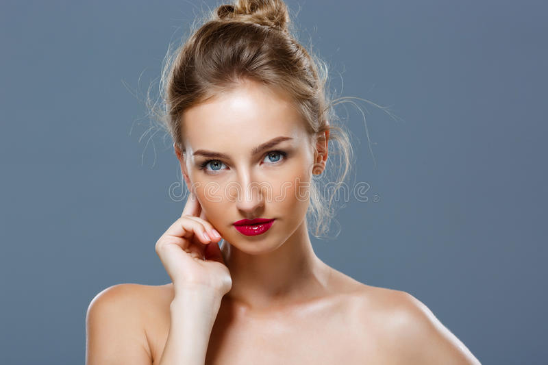 Beautiful blonde girl with bright makeup posing over grey background. royalty free stock image