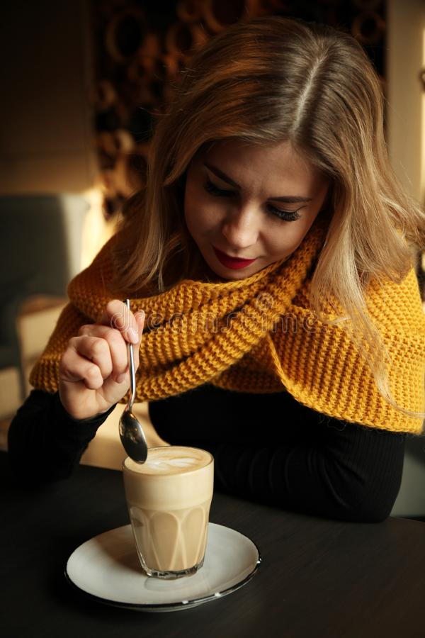 Beautiful blonde girl in cafe or restaurant drinking morning coffee royalty free stock images