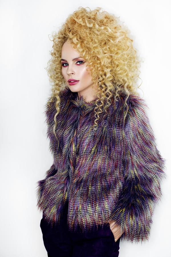 Girl with curly hair. Beautiful blonde girl with curly hair in purple fur coat on white smiling background royalty free stock images