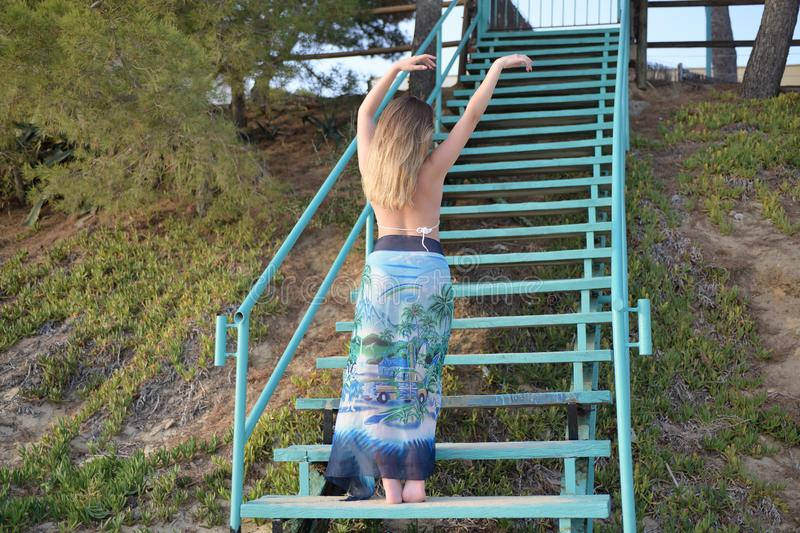 Beautiful blonde girl dances slow and sensually on stairs back to the camera with raised arms royalty free stock photos