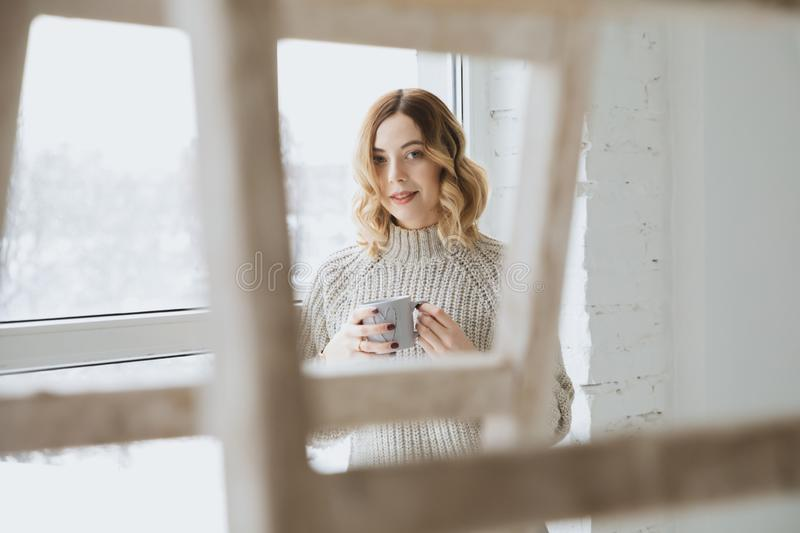 Beautiful blonde girl drinking tea by the window. royalty free stock images