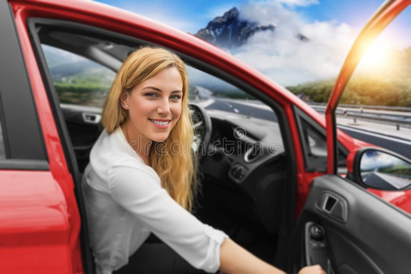 Beautiful blonde girl driving a car on the highway. Invitation to travel. Car rental or vacation. stock photo