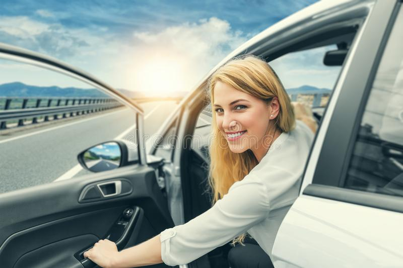 Beautiful blonde girl driving a car on the highway. Invitation to travel. Car rental or vacation. royalty free stock photos