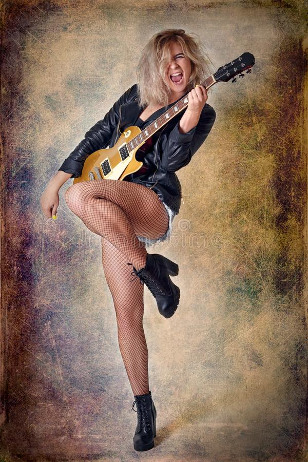 Beautiful blonde girl emotionally plays guitar. The texture of background is scratched. stock image