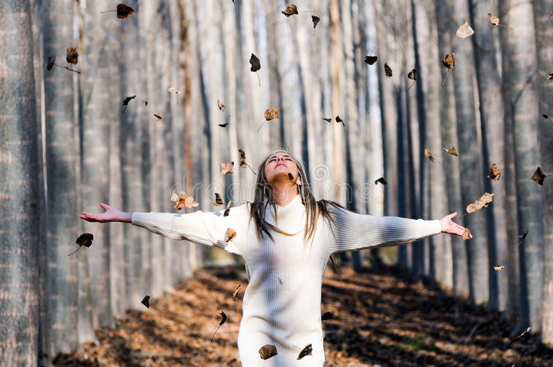 Beautiful blonde girl with falling leaves royalty free stock photography