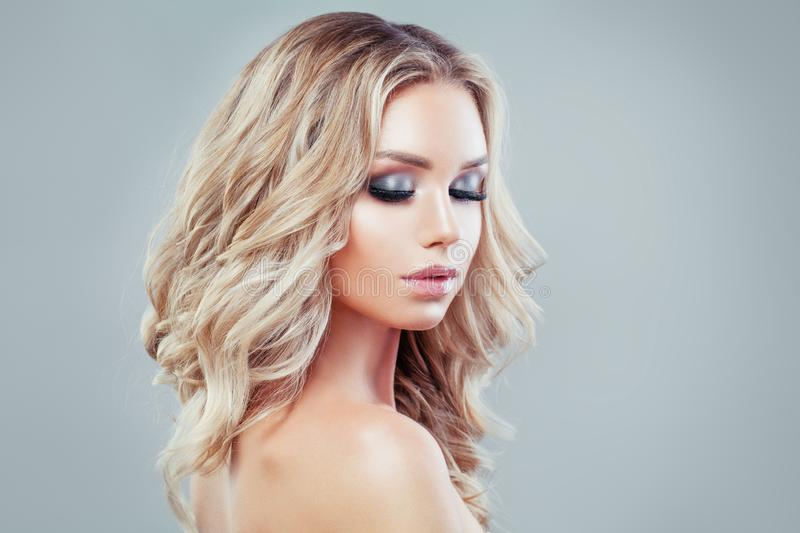 Beautiful blonde girl fashion model with long curly hair royalty free stock image