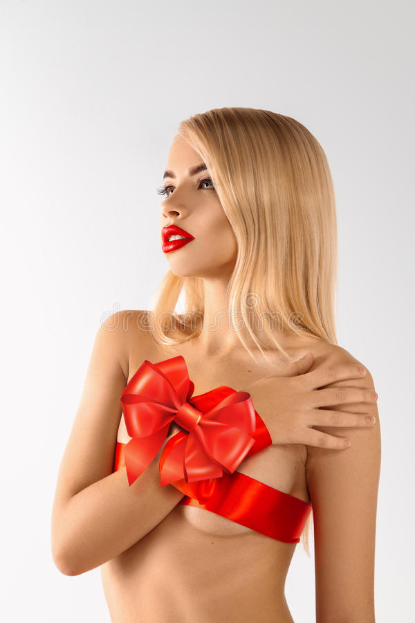 Beautiful blonde girl-gift with healthy skin and red ribbons on stock photos
