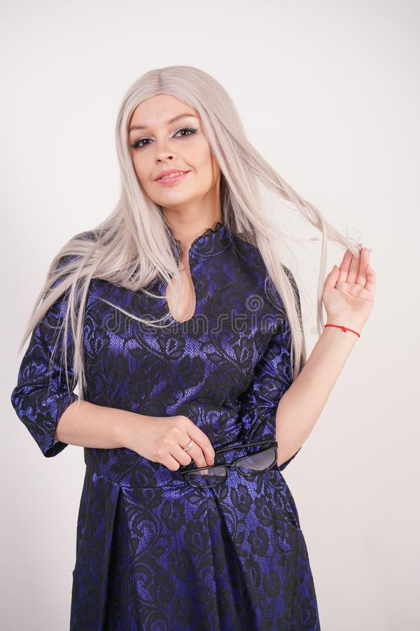 Beautiful blonde girl with glasses in luxurious blue with black lace evening dress on white background in Studio. Isolated royalty free stock photos