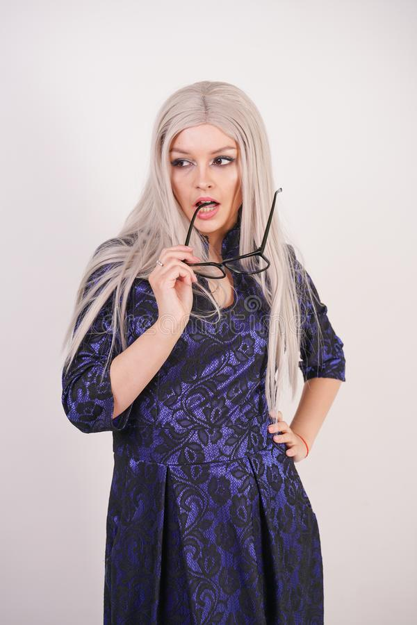Beautiful blonde girl with glasses in luxurious blue with black lace evening dress on white background in Studio. Isolated stock photography