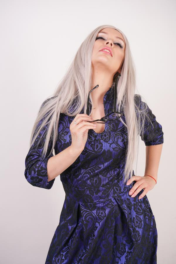 Beautiful blonde girl with glasses in luxurious blue with black lace evening dress on white background in Studio. Isolated stock photo