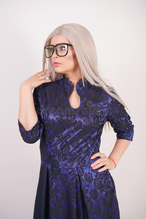 Beautiful blonde girl with glasses in luxurious blue with black lace evening dress on white background in Studio. Isolated royalty free stock image