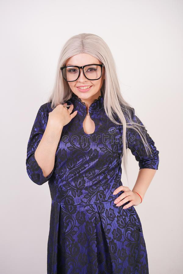 Beautiful blonde girl with glasses in luxurious blue with black lace evening dress on white background in Studio. Isolated stock photos