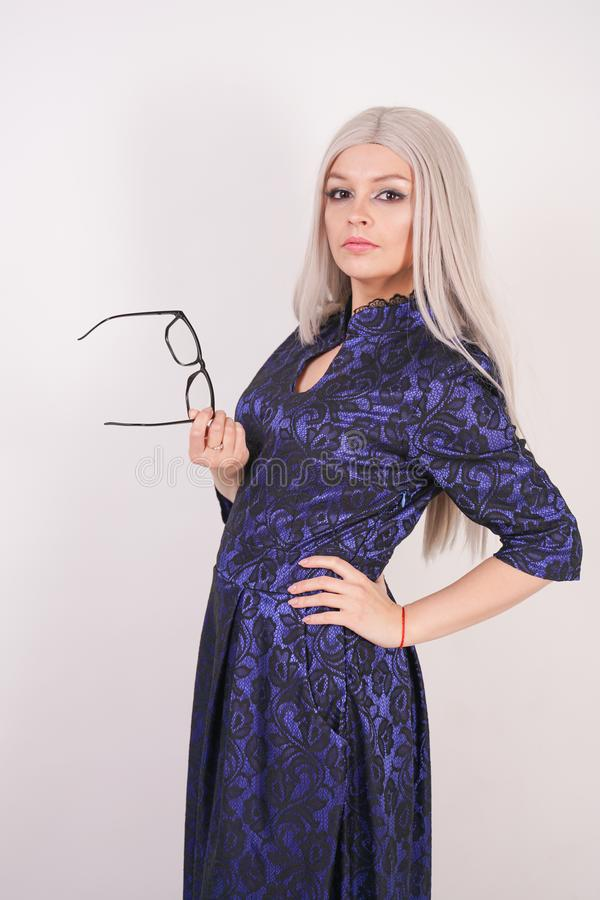 Beautiful blonde girl with glasses in luxurious blue with black lace evening dress on white background in Studio. Isolated royalty free stock photography