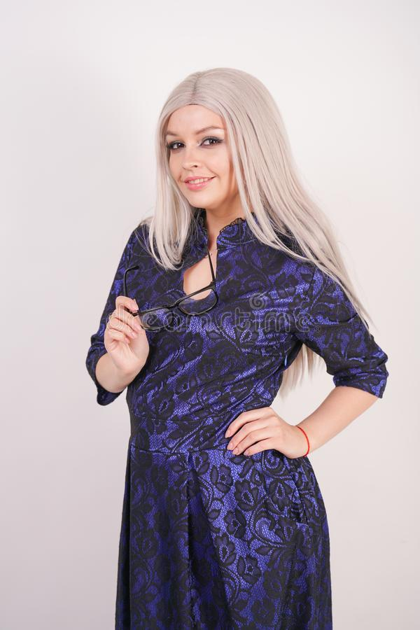 Beautiful blonde girl with glasses in luxurious blue with black lace evening dress on white background in Studio. Isolated stock images