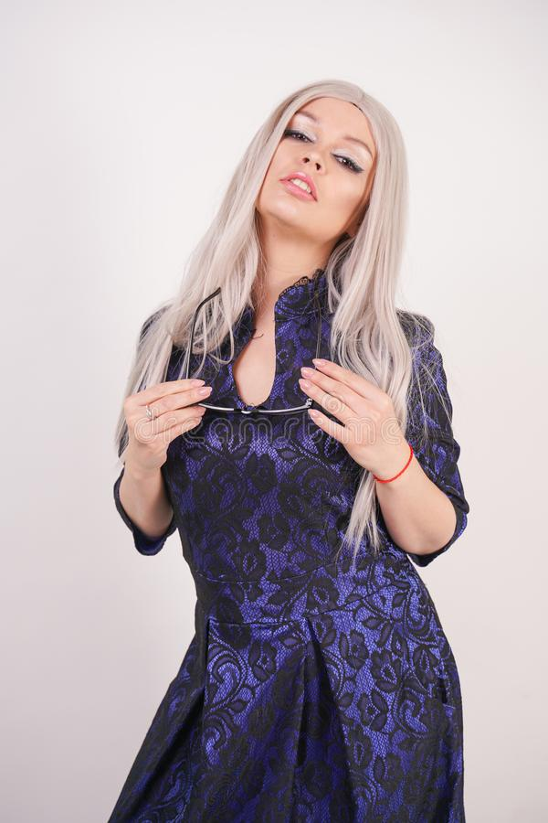 Beautiful blonde girl with glasses in luxurious blue with black lace evening dress on white background in Studio. Isolated royalty free stock photo