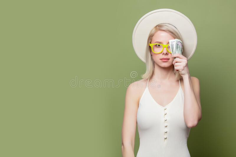 Beautiful blonde girl in glasses with money royalty free stock images