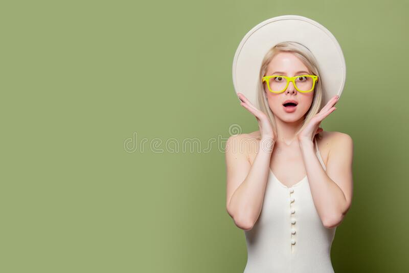 Beautiful blonde girl in glasses and white hat stock image