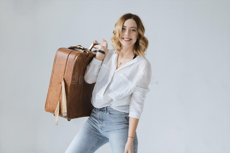 Beautiful blonde girl holding a large suitcase. royalty free stock images
