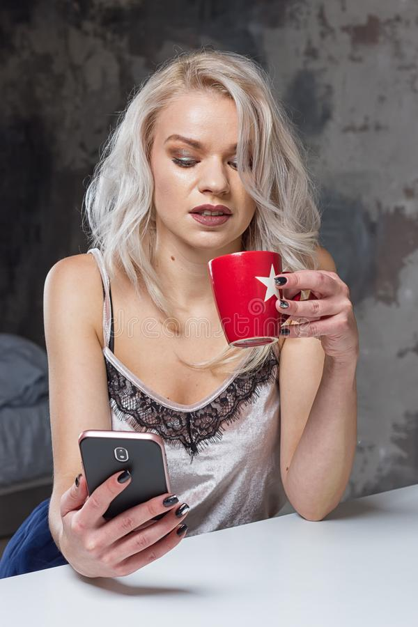 Beautiful blonde girl in home clothes is using a smartphone stock images