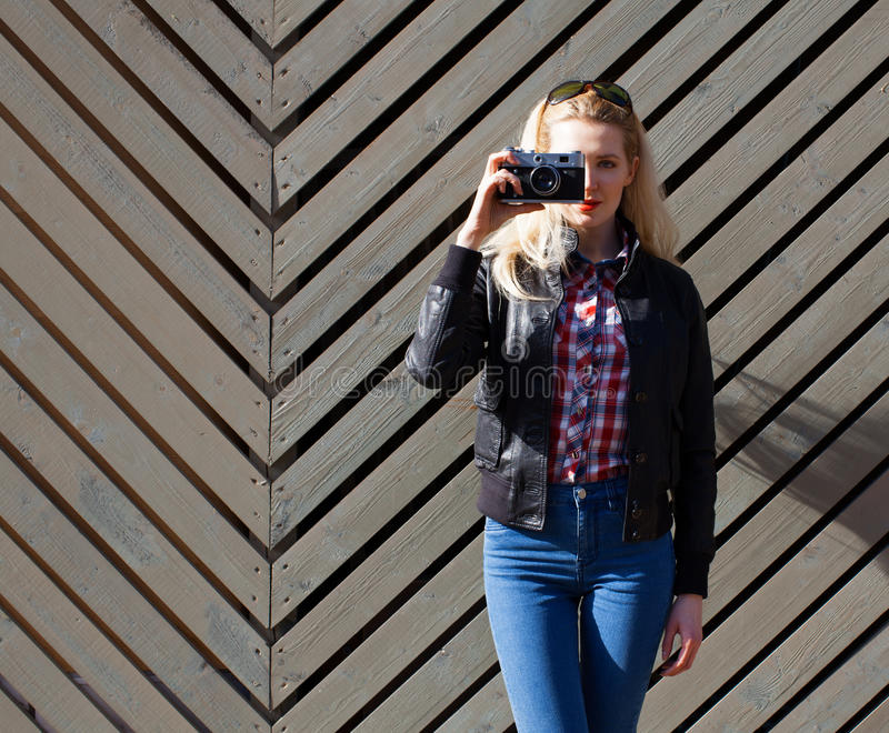 Beautiful blonde girl in huge sunglasses and a black jacket posing nex to wooden wall sunny day makes shoot vintage camera. Beautiful blonde girl in huge stock photo