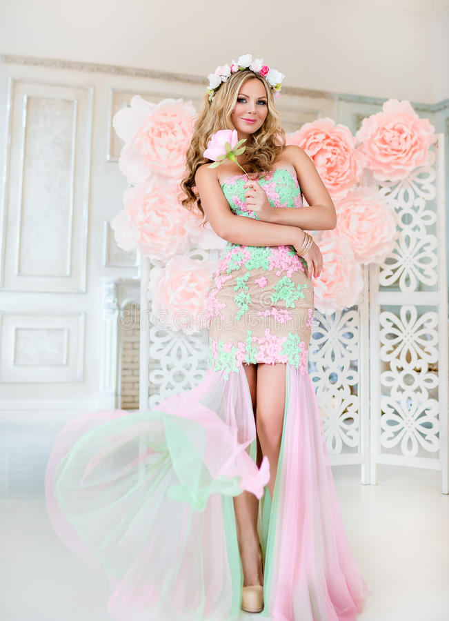 Beautiful blonde girl in a lace dress with a wreath of flowers o stock photos