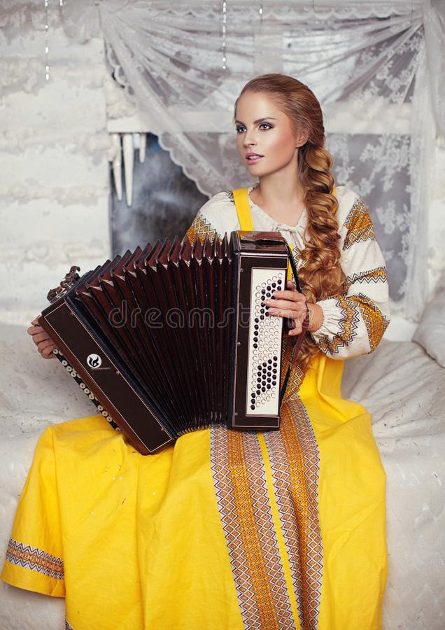 The girl with the accordion. Beautiful blonde girl with a long braid in a yellow sundress and an accordion in his hands stock photos