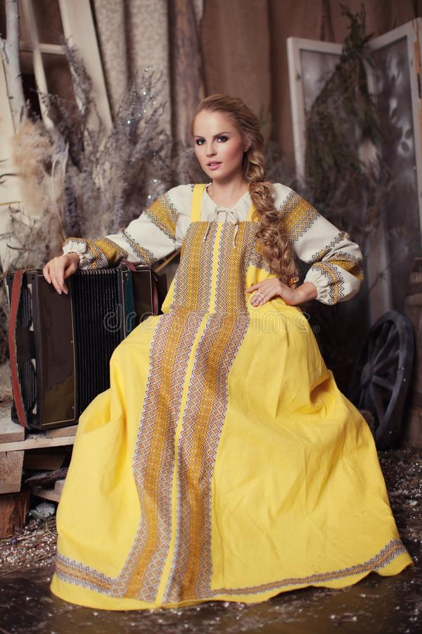 Beautiful blonde girl with long braid. In yellow sundress sitting with accordion royalty free stock photos