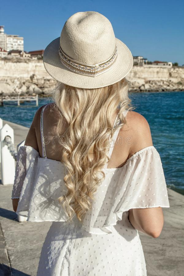Beautiful blonde girl, with long hair in a hat at the sea, stands with her back. royalty free stock images