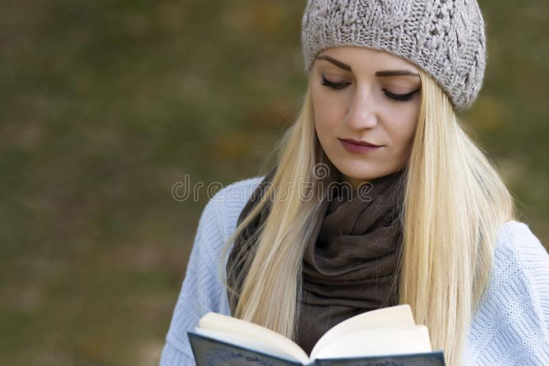 A beautiful blonde girl with long hair is reading a book. royalty free stock photo
