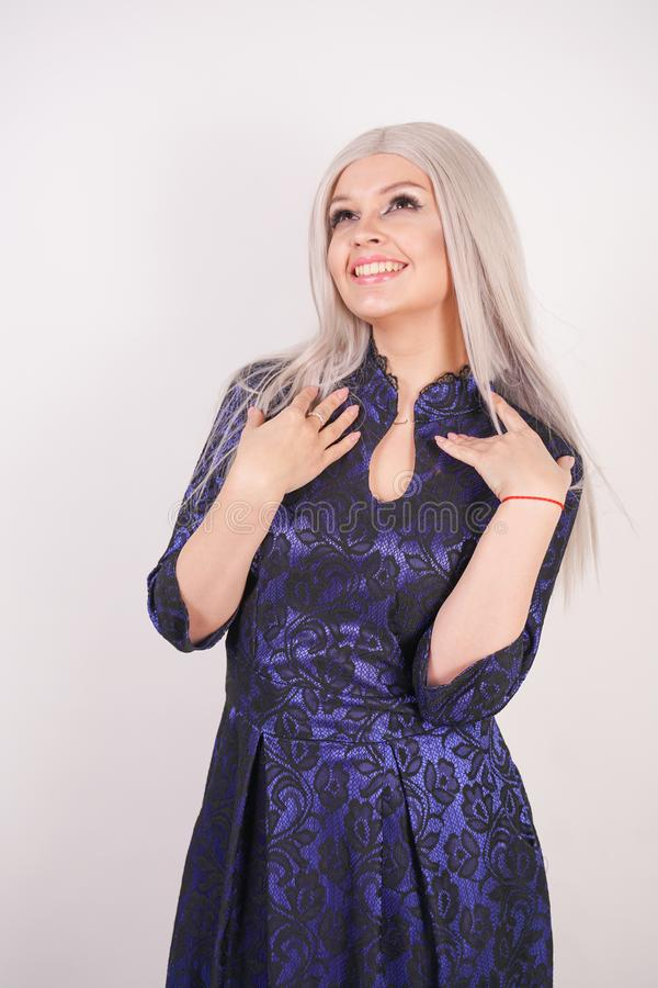 Beautiful blonde girl in luxurious blue with black lace evening dress on white background in Studio. Isolated royalty free stock photos