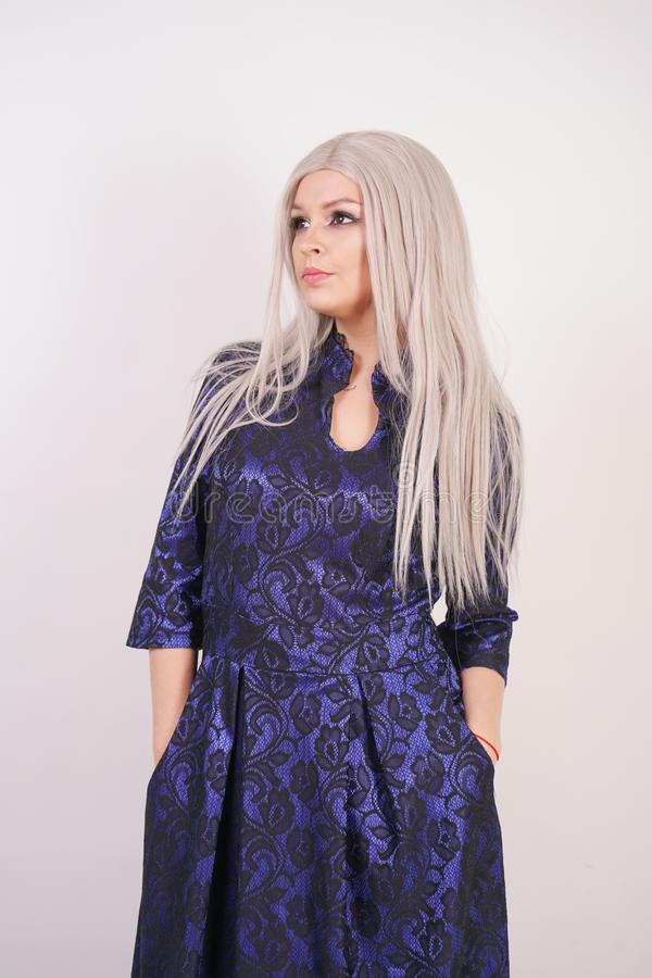 Beautiful blonde girl in luxurious blue with black lace evening dress on white background in Studio. Isolated stock photos